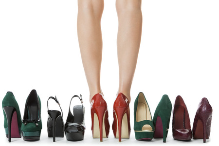 37300465 - close up flawless woman legs in glossy red high heel shoes standing between other elegant high heels. isolated on white background.